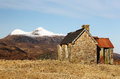 Ben more an old deserted stone hut on a hill with the mountain of in the distance from sutherland in the scottish highlands Royalty Free Stock Photo