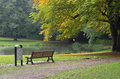 Bench in autumn park and trash bin a colorful Royalty Free Stock Photo