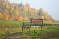 Bench in autumn with view to forest and lake Stock Photography