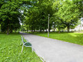 A bench at the city park alley. Royalty Free Stock Photo