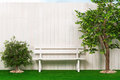 Bench by the fence with a tree and shrubs Stock Photography