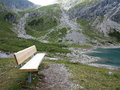 Bench in mountain massif scenery a wooden the rough landscape of the area at lake lünersee m above sea level austria picture Royalty Free Stock Photo