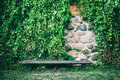 Bench near old stone wall covered with ivy leaves Royalty Free Stock Photo