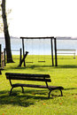 Bench in the park with swing on lake shore Royalty Free Stock Photos