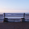 Bench and the sea in evening time Stock Photo