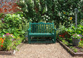 Bench seat in an english garden in early spring surrounded with summer flowers walled Stock Images