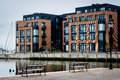 Benches and apartment building on the waterfront in Fells Point, Royalty Free Stock Photo