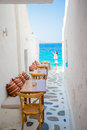 Benches with pillows in a typical greek outdoor cafe in Mykonos with amazing sea view on Cyclades islands Royalty Free Stock Photo