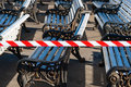 Benches in a public park are in preparation for the coming summe summer season caution tape warns people that still Royalty Free Stock Photography