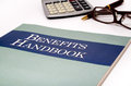 Benefits handbook close up of a with glasses pen and calculator in the background Stock Photo