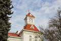 Benton county courthouse corvallis oregon the clock tower of against a blue and white cloud mottled sky trees frame the tower Royalty Free Stock Image