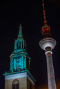 Berlin tv tower at night with a turret from a church Royalty Free Stock Photo