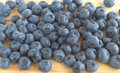 The berries of blueberry scattered on a cutting board