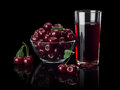 Berries of a cherry and juice on a black background the glass vase glass are isolated Stock Photos