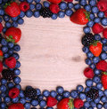 Berries frame on wooden background strawberries blueberry raspberries and blackberry Royalty Free Stock Photo