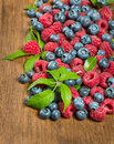 Berries on wooden background mix of fresh with leaves Stock Photography