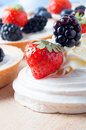 Berry fruit meringues and tartlets close up of a meringue with swirls of fresh cream fruits strawberry blackberry on a wooden Royalty Free Stock Photo