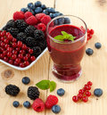 Berry smoothie a glass of with fresh fruits shallow depth of field Royalty Free Stock Photography