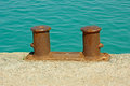 Berth rusty bitts steel dual mooring bitt on a fragment of old concrete pier on the background turquoise sea water in calm Royalty Free Stock Photography