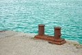 Berth rusty steel bitts dual mooring bitt on a fragment of old concrete pier on the background turquoise sea water Stock Photos