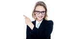 Bespectacled business girl pointing away young leader at something Royalty Free Stock Images