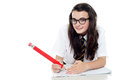 Bespectacled schoolgirl with long hair studying Royalty Free Stock Photo