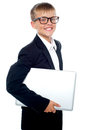 Bespectacled young boy carrying a laptop Stock Photos