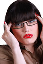 Bespectacled young brunette with bloodshot lips and fingers to temples Stock Photo