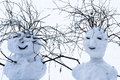 Best christmas wishes from mister and missis snowball two smiling snowmen with hair style of dry twigs against white snowy Stock Photos