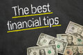 The best financial tips text on blackboard with money Royalty Free Stock Photos