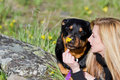 Best firends woman and her dog resting in the spring grass with yellow flowers showing affection Stock Photography