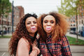 Best friends chewing bubble gum happy young women blowing outdoors Stock Photo