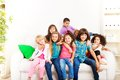 Best friends forever group of seven happy little years old kids boys and girls black asian and caucasian sitting on the coach Royalty Free Stock Photo