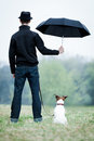 Best friends friendship between dog and owner standing in the rain with umbrella Stock Photo