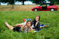 Best friends having a picnic next to their car Royalty Free Stock Photo