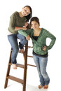 Best friends portrait of two beautiful young teens in casual clothes posed with an old ladder Royalty Free Stock Photo