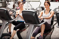 Best friends in spinning class happy female working out together a at the gym Royalty Free Stock Images