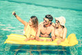 Best friends taking selfie at swimming pool with yellow airbed Royalty Free Stock Photo