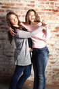 Best friends two pretty bff brunette teenage girls horsing around in front of a brick wall Royalty Free Stock Photos