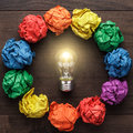 Best idea concept with crumpled colorful paper circle and light bulb in the centre on wooden table Royalty Free Stock Photography