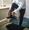 Best man getting ready for a special day a groom putting on shoes as he gets dressed in formal wear groom s suit Royalty Free Stock Image