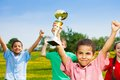 Best at sport close shoot of black happy smiling little boy holding prize cup in lifted hands Royalty Free Stock Images
