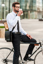 The best way to start a day side view of handsome young businessman drinking coffee while sitting on his bicycle Royalty Free Stock Photography
