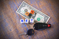 Bet currency keys the word spelled out on a one dollar bill money with dice and vehicle on burlap as a background Royalty Free Stock Image
