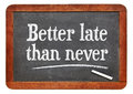 Better late than never proverb white chalk text on a vintage slate blackboard Stock Image