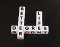 Better life with a degree text inscribed in black letters on small white cubes arranged crossword style to indicate leads to Royalty Free Stock Photo