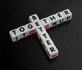 Better together campaign slogan text and in black uppercase letters inscribed on small white cubes and arranged crossword style Royalty Free Stock Photography