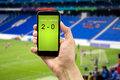Betting on the winner man through his smart phone in a stadium Stock Photos