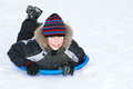 Beuatiful child wearing winter clothes sledding on snow having fun Royalty Free Stock Images