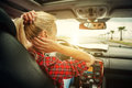 Beutiful blond girl comb her hair with a rearview mirror in car Royalty Free Stock Photo